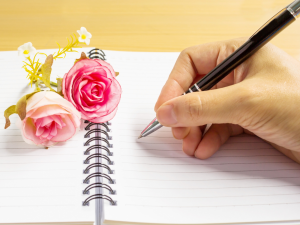 a close-up image of a person writing on a notebook